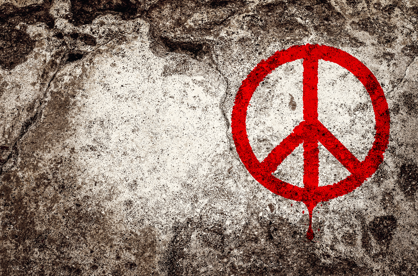 Red peace symbol graffiti on grunge cement wall - peace concept